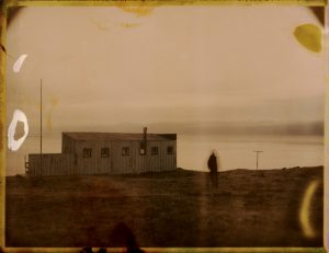 hooded person stands by an abandoned farm at sunset in iceland - arctic midnight sun - fine art polaroid photography by Guðmundur Óli Pálmason Kuggur.com