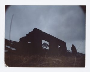 dark silhouette of a hooded person stands by an abandoned farm in iceland - fine art polaroid photography by Guðmundur Óli Pálmason Kuggur.com