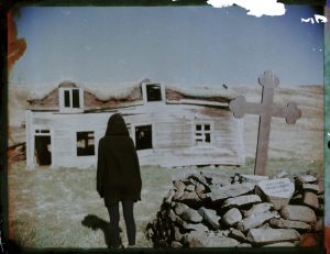 hooded person and cross in front of an abandoned traditional turf house church in Iceland Fine art Polaroid photography by Guðmundur Óli Pálmason kuggur.com