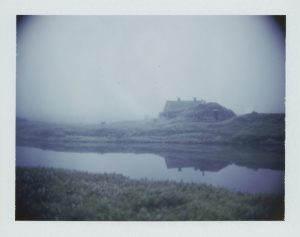 turf house farm in the fog in Iceland reflects in still water midnight sun Fine art Polaroid photography by Guðmundur Óli Pálmason kuggur.com turf