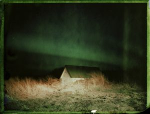 a small shed under the northern lights in Iceland - aurora borealis - fine art polaroid photography by Guðmundur Óli Pálmason - kuggur.com