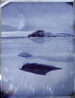 an opening in the ice of frozen lake Mývatn in Iceland - landscape photography - fine art polaroid photography by Guðmundur Óli Pálmason - kuggur.com