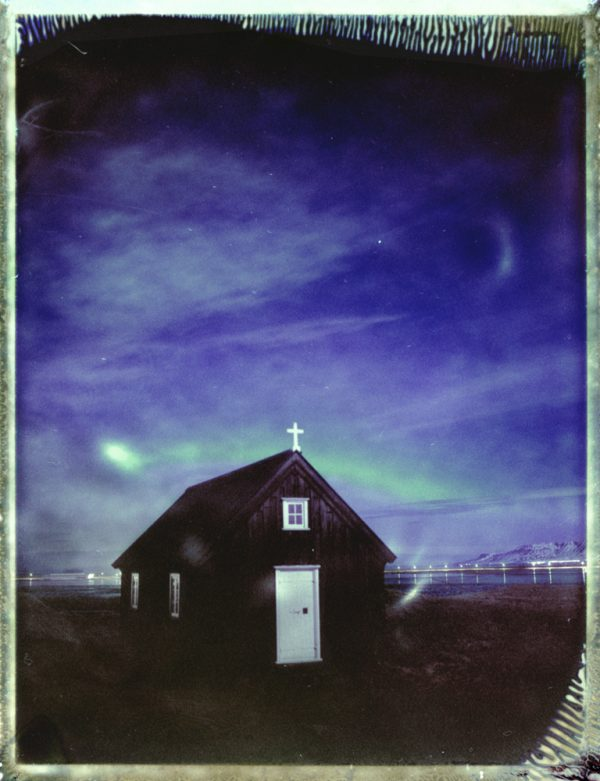 a small church under the northern lights in Iceland - aurora borealis - fine art polaroid photography by Guðmundur Óli Pálmason - kuggur.com