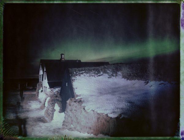 a traditional Icelandic turf house under the northern lights in Iceland - aurora borealis - fine art polaroid photography by Guðmundur Óli Pálmason - kuggur.com