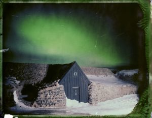 a traditional Icelandic turf house under the northern lights in Iceland - aurora borealis - fine art polaroid photography by Guðmundur Óli Pálmason - kuggur.com