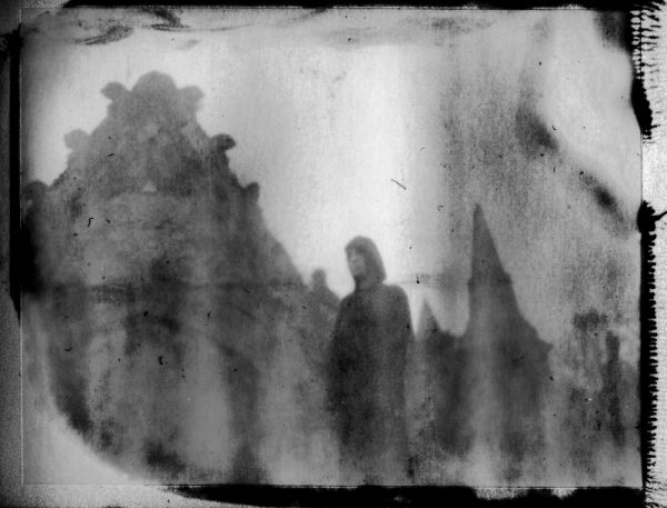 a dark figure of death by an abandoned tomb - corona art - fine art polaroid photography by Guðmundur Óli Pálmason - kuggur.com
