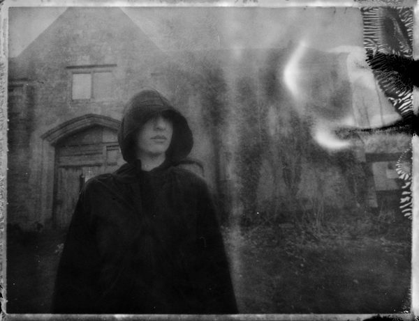 a dark figure of death by an abandoned mansion - corona art - fine art polaroid photography by Guðmundur Óli Pálmason - kuggur.com