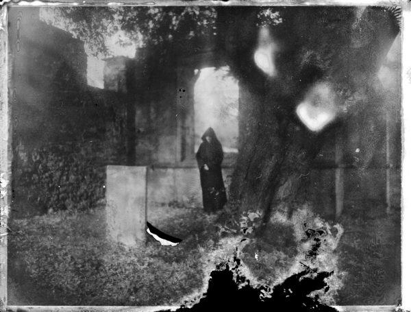 a dark figure of death by a grave at an abandoned church - corona art - fine art polaroid photography by Guðmundur Óli Pálmason - kuggur.com